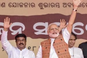Prime Minister Narendra Modi with Petroleum Minister Dharmendra Pradhan waves at the crowd at a public meeting after the inauguration of Jharsuguda airport in Odisha, Saturday, September 22, 2018.