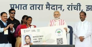 Prime Minister Narendra Modi gives a health card to beneficiaries as he launches Ayushman Bharat-National Health Protection Scheme