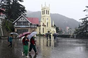 People take a stroll with umbrellas during rain at Ridge, Shimla on Saturday, September 22. 2018.