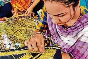 A student preparing a wall hanging from crop waste at PAU in Ludhiana.