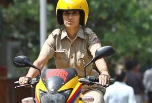 A woman police constable patrols on a Motor Bike at the South Campus Delhi University.