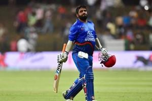 Afghanistan batsman Mohammad Shahzad (R) leaves the pitch after being dismissed during the one day international (ODI) Asia Cup cricket match between Afghanistan and Bangladesh.