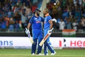 Indian cricket team captain Rohit Sharma (L) and his teammate Shikhar Dhawan greet each other during the one day international (ODI) Asia Cup cricket match between Pakistan and India at the Dubai International Cricket Stadium in Dubai on September 23, 2018. (Photo by ISHARA S. KODIKARA / AFP)