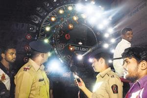 Police personnel check the noise during the immersion procession of a Ganpati mandal with a decibel measuring device in Pune, on Friday.