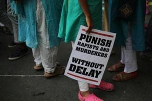 A protestor stands with a placard during a protest against two recently reported rape cases as they gather near the Indian parliament in New Delhi, India