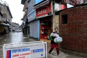 A shopkeeper carries goods down a flooded road in Srinagar after heavy rainfall.