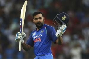 Rohit Sharma raises his bat and helmet to celebrate scoring a century during Asia Cup 2018 match against Pakistan.