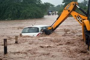 A JCB machine lifting a car that got stuck in an overflowing rivulet near Dadumajra in Chandigarh on Monday.