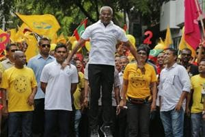 Ibrahim Mohamed Solih, centre, jumps as he walks in a street march with supporters in Male, September 22
