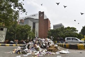 Municipal workers protested by pilling garbage to press for their various demands including pay scales at outer circle, Connaught place.