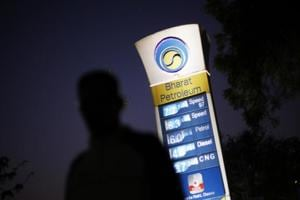 A Bharat Petroleum oil pump station displays the price of unleaded petrol and Diesel as a pedestrian walks past in New Delhi.