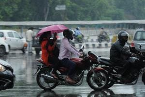 Commuters protect themselves from rain using umbrellas and raincoats at Rajiv Chowk, in Gurugram, India, on Monday, September 24, 2018.
