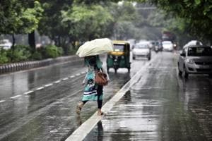 A commuter crosses a road near Africa Avenue road, as it rains in New Delhi on September 24.