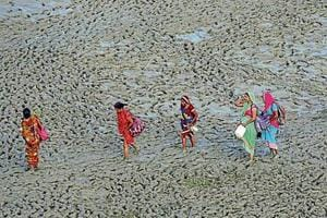 People walk along the muddy banks of River Ganga in Allahabad