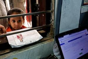 A girl waits for her turn to enrol for the Unique Identification database system, also known as Aadhaar, at a registration centre in New Delhi.