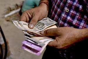 A man counts notes at a fuel station, in Kolkata on  August 14.