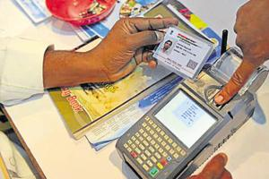 A man gives a thumb impression to withdraw money from his bank account with his Aadhaar card in Hyderabad.
