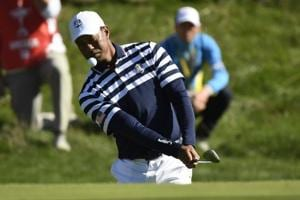 US golfer Tiger Woods plays a chip shot during a practice session ahead of the 42nd Ryder Cup at Le Golf National Course at Saint-Quentin-en-Yvelines