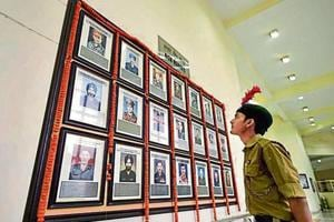 An NCC cadet looks at portraits of fallen soldiers during an event to celebrate the second anniversary of the surgical strike at Jawaharlal Nehru University on Saturday.
