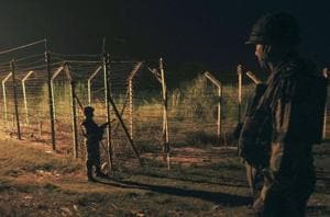 Border Security Force (BSF) soldiers standing guard during a night patrol near the fence at the India-Pakistan International Border at the outpost of Akhnoor sector, about 40 km from Jammu.