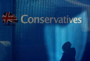 The silhouette of an arrival at the conference centre, is seen on a barrier positioned on the perimeter ahead of the Conservative Party Conference in Birmingham.