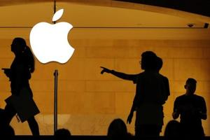 Customers walk past an Apple logo inside of an Apple store at Grand Central Station in New York.