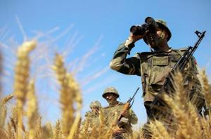 Border Security Force (BSF) personnel uses binoculars to maintain vigil along the International Border in Jammu.