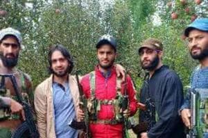 Adil Bashir, who is wearing a red jacket in this photo, is pictured standing with alleged Hizbul Hizbul Mujahideen militants.