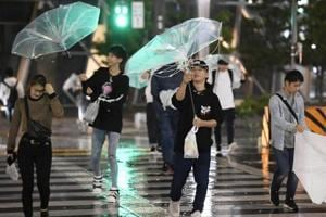 Passersby using umbrellas struggle against strong wind and rain caused by Typhoon Trami in Nagoya, central Japan on September 30, 2018.