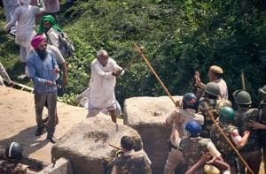An elderly farmer clashes with police personnel during a protest at Delhi-UP border during