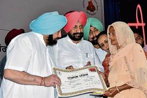 Chief minister Captain Amarinder Singh handing over a certificate to a government scheme beneficiary in Mohali on Tuesday.