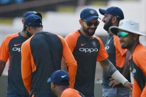 Indian cricket captain Virat Kohli (C) jokes with teammates as he arrives for a training session ahead of the first Test cricket match between India and West Indies at the Saurashtra Cricket Association stadium in Rajkot