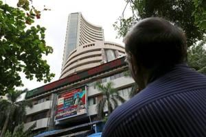 A man looks at a screen across a road displaying the Sensex on the facade of the Bombay Stock Exchange (BSE) building in Mumbai, India, June 29, 2015.
