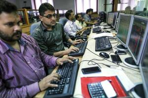 Employees work at computers at a brokerage firm in Mumbai.