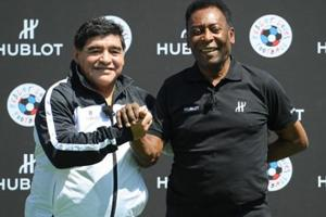 Pele (R) and Diego Maradona pose for a picture.