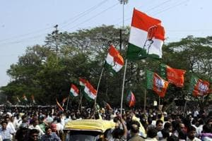 Congress and BJP supporters wave flags in a show of strength in Indore.