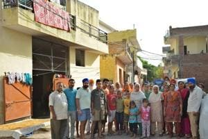Residents of Pabhat village outside their houses on Saturday. The Zirakpur MC has issued them a notice to vacate their houses, after which a demolition drive will be held on Monday.