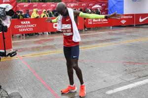 Mo Farah of Great Britain, raises his arms after he finishes in first place during the Bank of America Chicago Marathon.