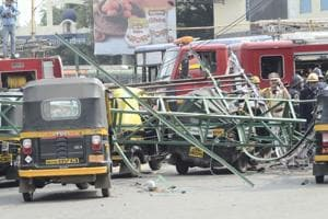 Four persons were killed while seven others injured when a 40-foot metal hoarding frame put up at the railway department's land collapsed when it was being cut.