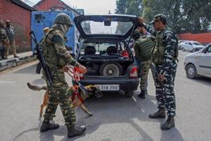 CRPF personnel check vehicles using sniffer dogs ahead of polling for first phase of elections for urban local bodies in Jammu and Kashmir, in Srinagar.