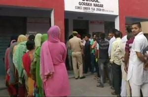 People queue outside a polling booth in Gorakh Nagar in Jammu.