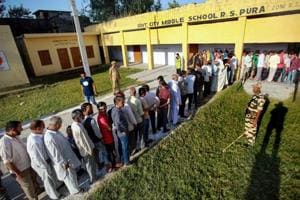 Jammu: Security persoonel stands guard as people wait in queues to cast their votes for muncipal elections in Ranbir Singh Pura near Jammu, Monday, Oct 8, 2018. (PTI Photo) (PTI10_8_2018_000026B)