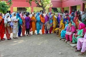 People wait in a queue to cast their votes at a polling station during municipal elections in Jammu, on Monday.