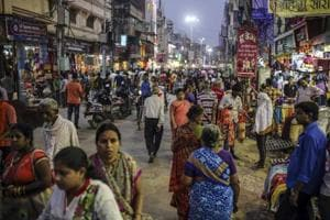 Pedestrians and shoppers walk past stores on a street in Varanasi, Uttar Pradesh. Advance estimates for 2014-15 released in February projected India's GDP during the year to grow at 7.4%, making it the world's fastest growing economy surpassing China.