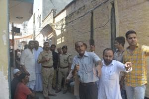 Locals speak to the police officers in Muradnagar where the body of a six year old girl was found on the roof of a mosque court on Sunday October 07, 2018.