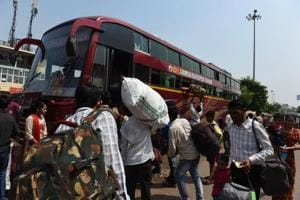 Wokers from Uttar Pradesh state board a buses as they leave in Ahmedabad on October 9.