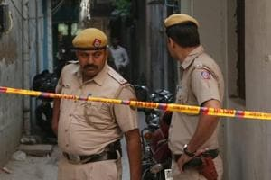Delhi Police cordon off the crime scene in Vasant Kunj where three of a family were found stabbed to death inside their home.
