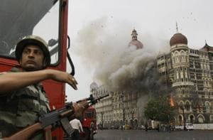 A soldier takes cover as the Taj Mahal hotel burns during a gun battle between the military and militants inside the hotel in Mumbai, on November 26, 2009. India blamed the Laskhar-e-Taiba for the attack, in which 174 were killed.