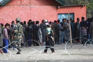 People queue up to vote outside a polling booth in Bandipora district, north of Srinagar, during the second phase of local bodies' elections, 10 October 2018.