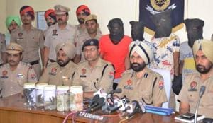 Ludhiana commissioner of police Sukhchain Singh Gill with other officers with the accused (face covered) in Ludhiana.
